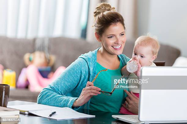 Caucasian mom uses laptop while holding baby girl