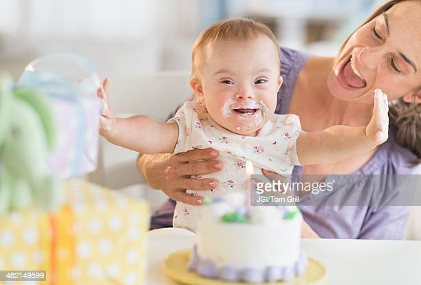 Caucasian mother and baby girl with Down Syndrome celebrating birthday