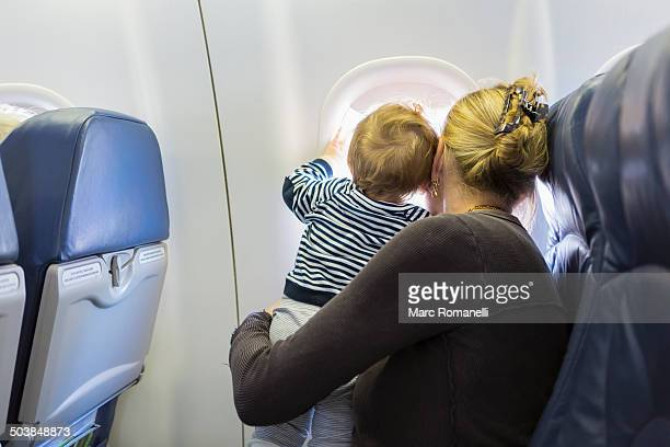 Caucasian mother and baby looking out airplane window
