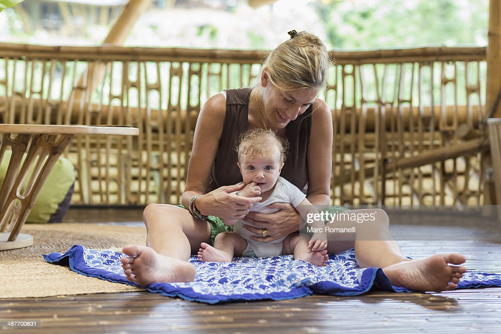 Caucasian mother and baby sitting on floor : Stock Photo