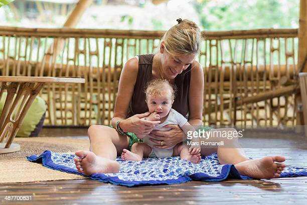 Caucasian mother and baby sitting on floor
