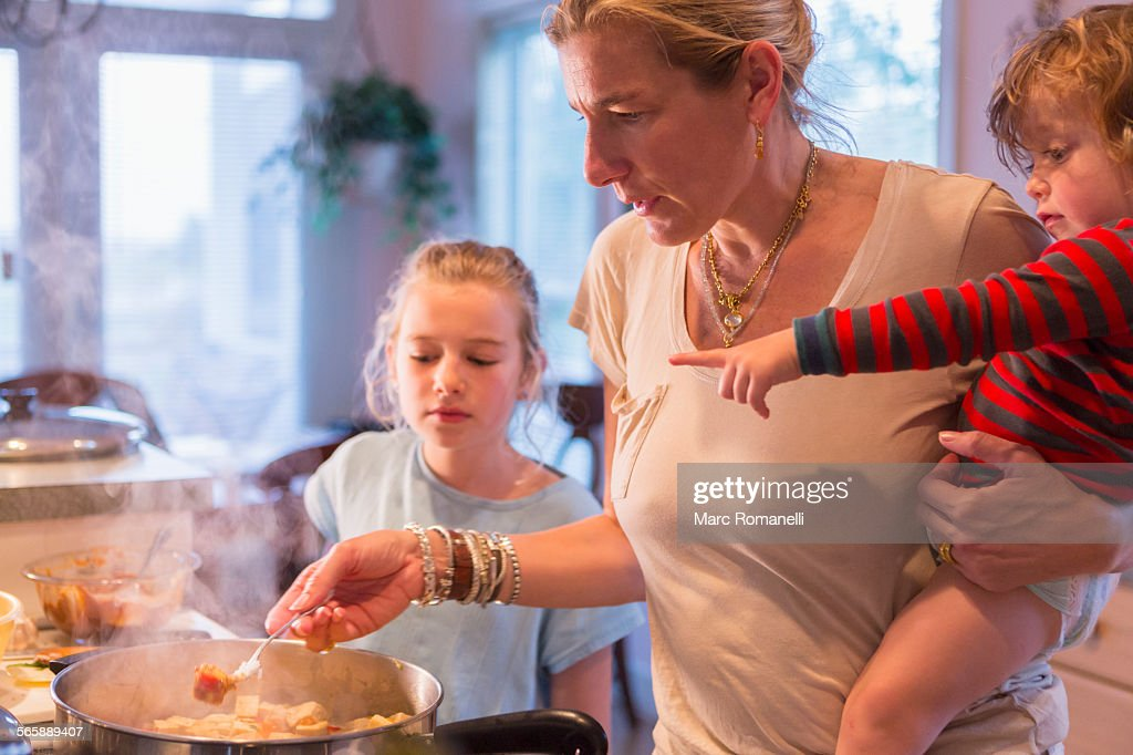 Caucasian mother and children cooking in kitchen : Photo