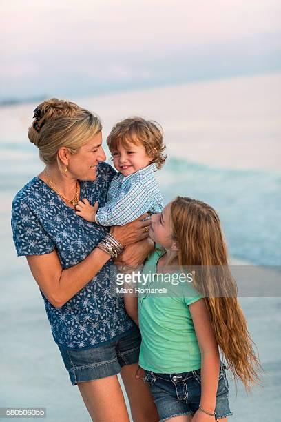 Caucasian mother and children playing on beach