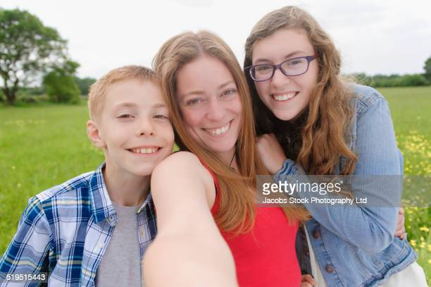 Caucasian mother and children taking cell phone selfie in field
