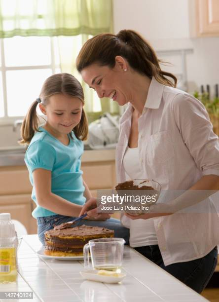 Caucasian mother and daughter baking a cake