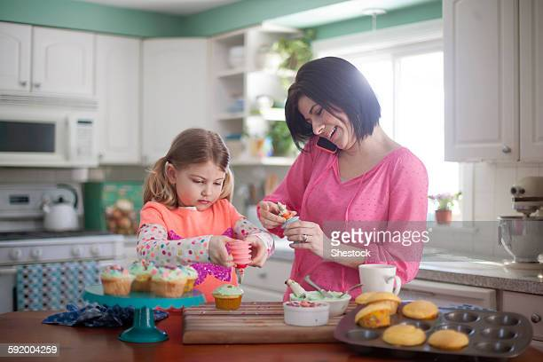 Caucasian mother and daughter baking in kitchen