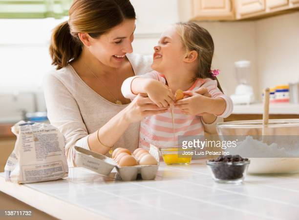 Caucasian mother and daughter baking together
