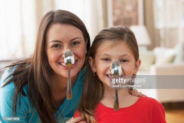 Caucasian mother and daughter balancing spoons on noses