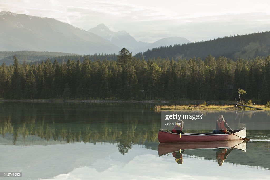 Caucasian mother and daughter canoeing on Lake Edith : Stock Photo