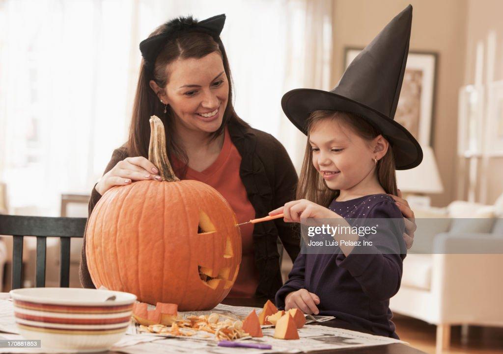 Caucasian mother and daughter carving pumpkin