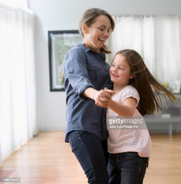 Caucasian mother and daughter dancing together