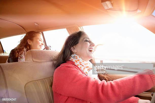 Caucasian mother and daughter driving in car