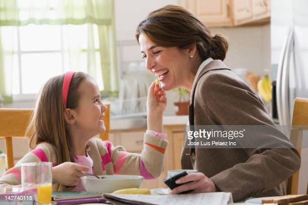 Caucasian mother and daughter eating breakfast
