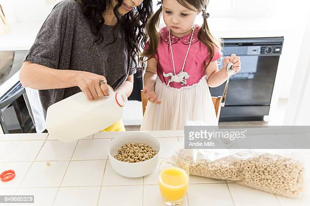 Caucasian mother and daughter eating cereal in kitchen