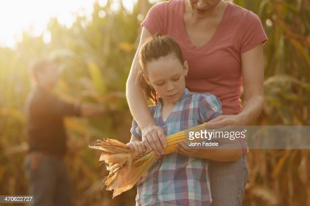 Caucasian mother and daughter examining ear of corn