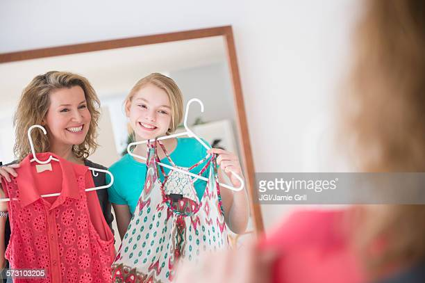 Caucasian mother and daughter examining shirts in mirror