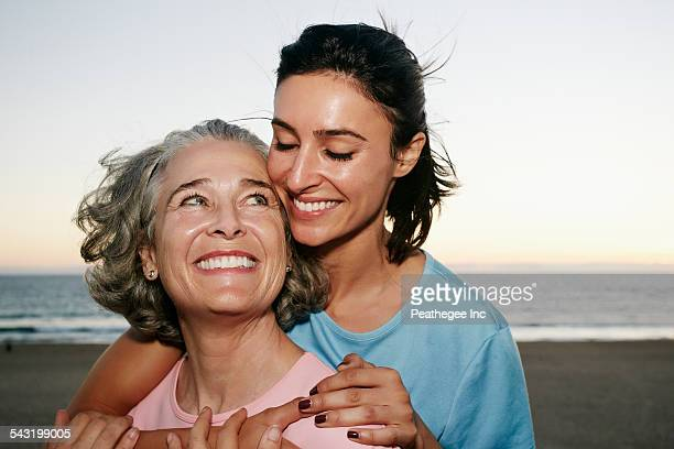 Caucasian mother and daughter hugging at beach