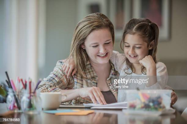 Caucasian mother and daughter hugging at table