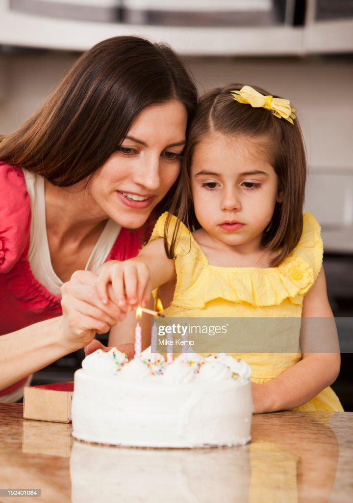 Caucasian mother and daughter lighting birthday candles : Stock Photo