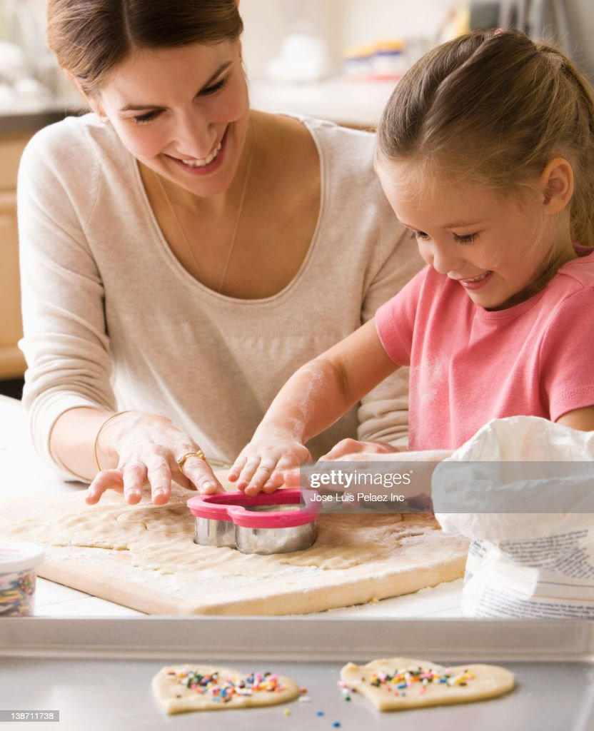 Caucasian mother and daughter making Valentine cookies : Stock Photo