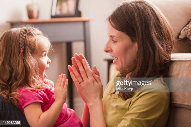 Caucasian mother and daughter playing clapping game