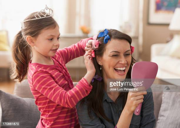 Caucasian mother and daughter playing dress up
