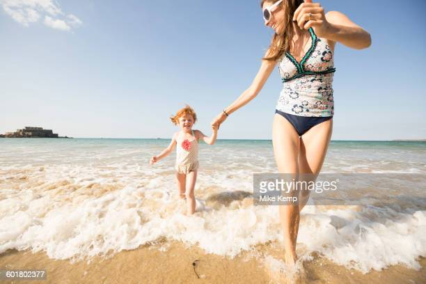Caucasian mother and daughter playing in waves on beach
