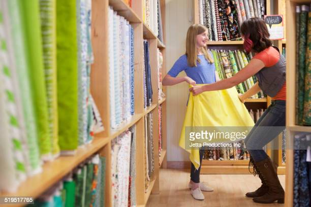 Caucasian mother and daughter shopping in fabric store