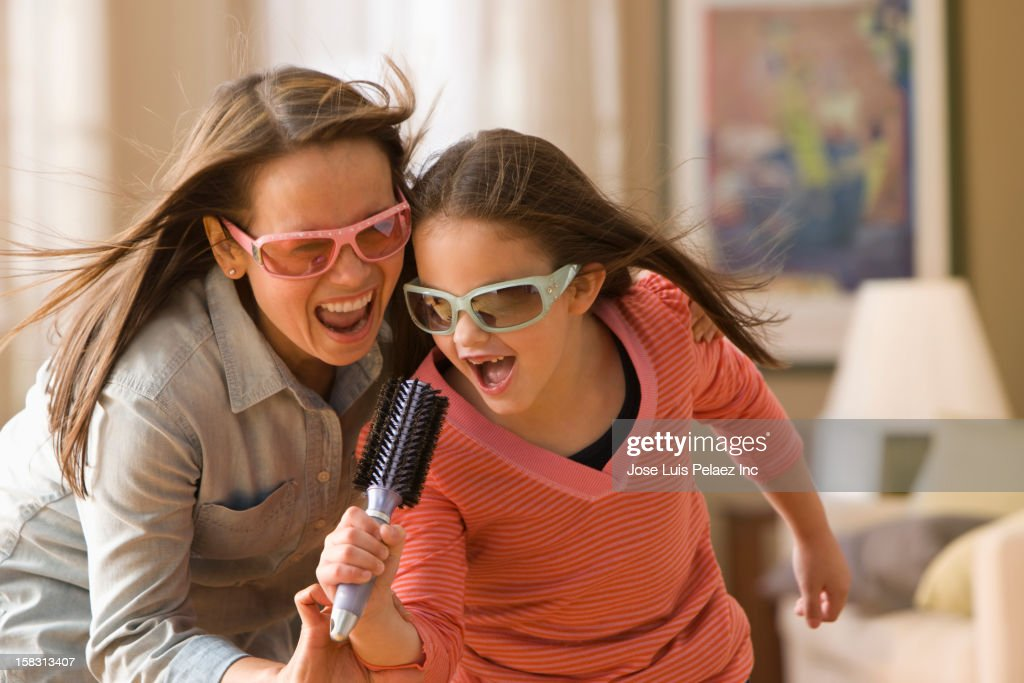 Caucasian mother and daughter singing into hairbrush