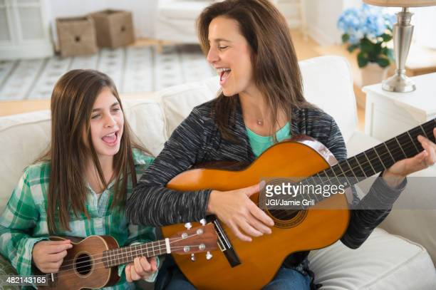 Caucasian mother and daughter singing with guitar and ukulele