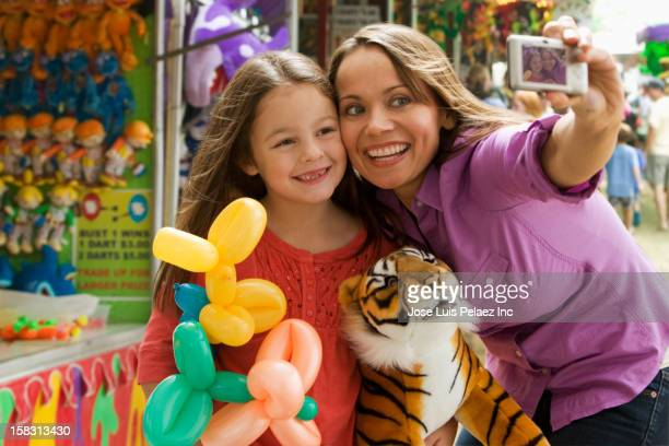 Caucasian mother and daughter taking self-portrait at fair