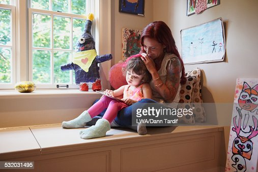 Caucasian mother and daughter using digital tablet : Stock Photo