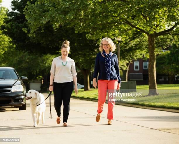 Caucasian mother and daughter walking dog on suburban street