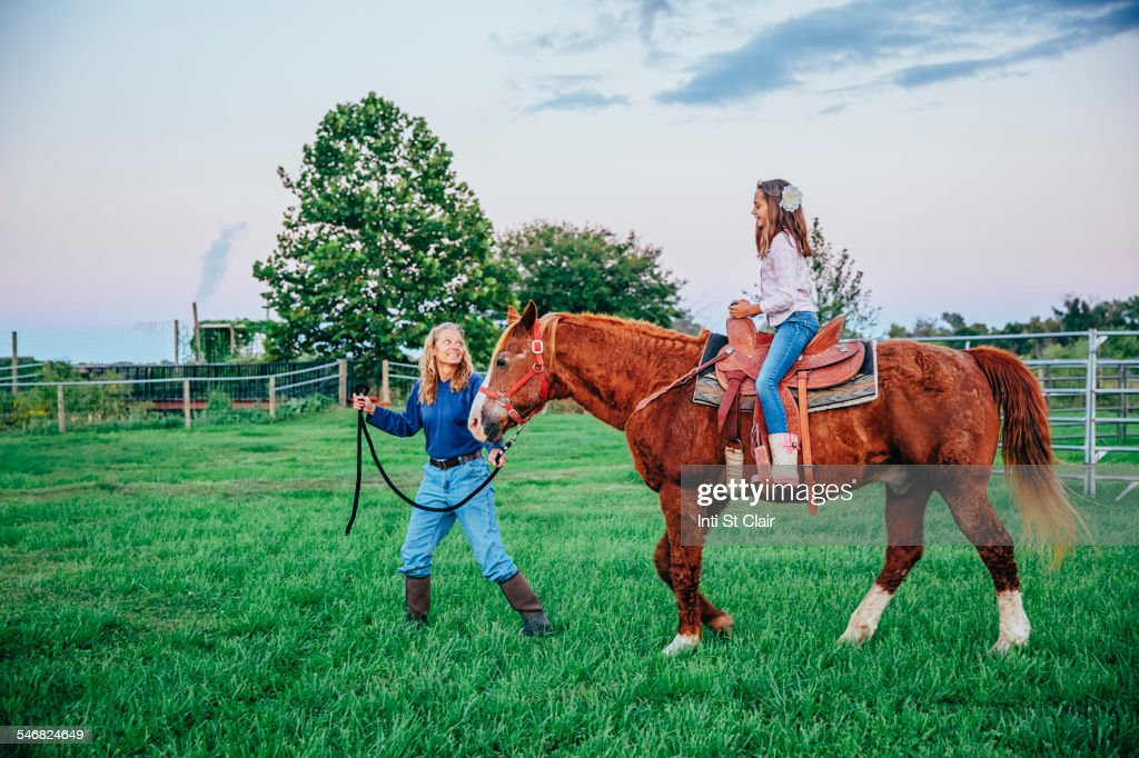 Caucasian mother and daughter walking horse on ranch