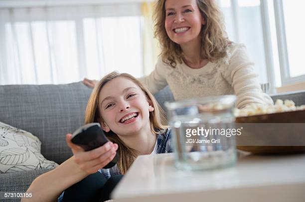 Caucasian mother and daughter watching television on sofa
