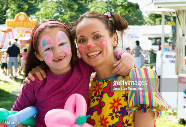 Caucasian mother and daughter with faces painted at fair