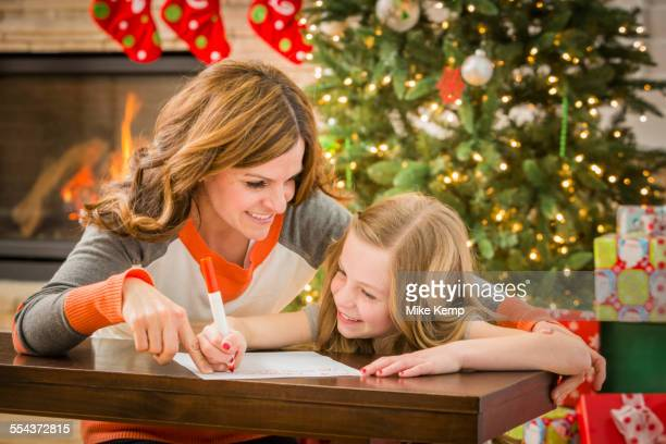 Caucasian mother and daughter writing to Santa at Christmas