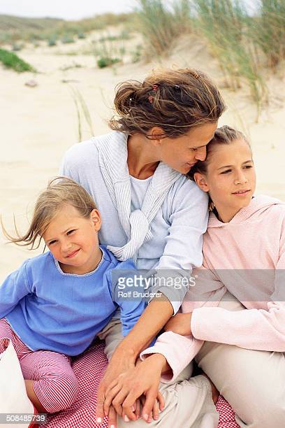 Caucasian mother and daughters hugging on beach