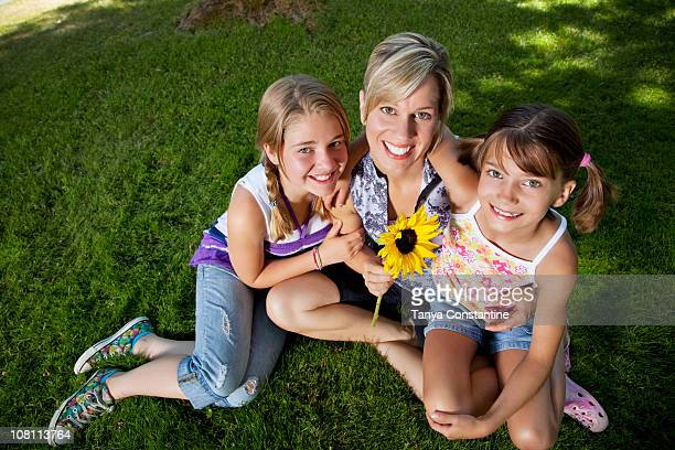 Caucasian mother and daughters sitting grass