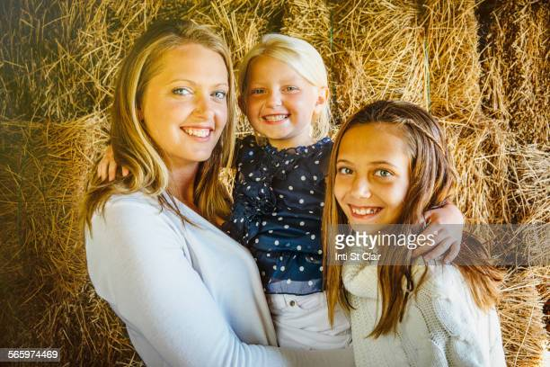 Caucasian mother and daughters smiling near haystacks