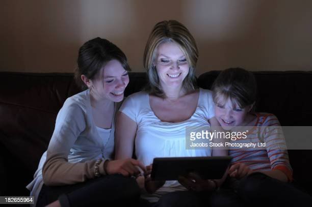 Caucasian mother and daughters using tablet computer together