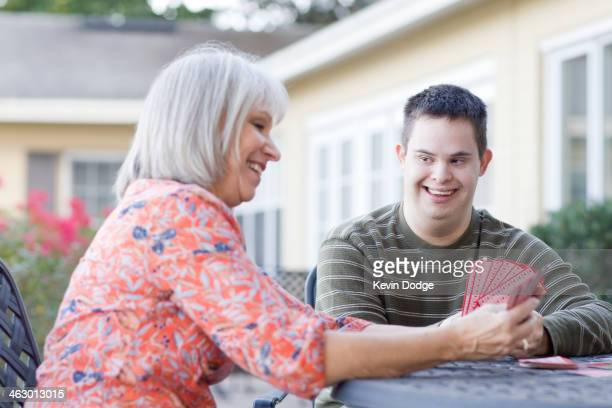 Caucasian mother and disabled son playing cards