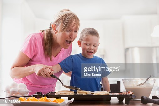 Caucasian mother and son cooking breakfast : Stock Photo
