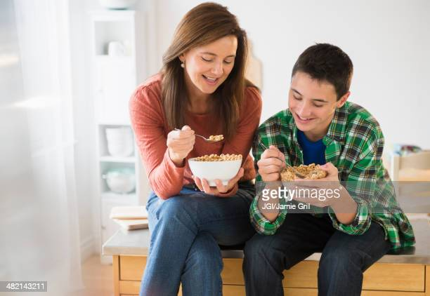 Caucasian mother and son eating cereal together