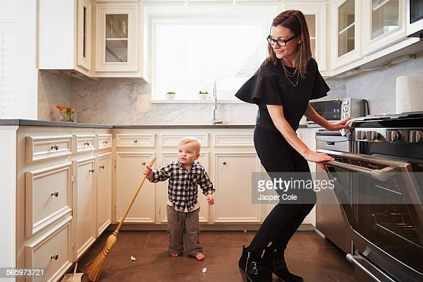 Caucasian mother and son holding broom kitchen