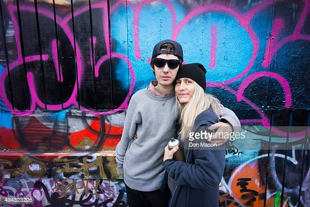 Caucasian mother and son hugging by graffiti wall