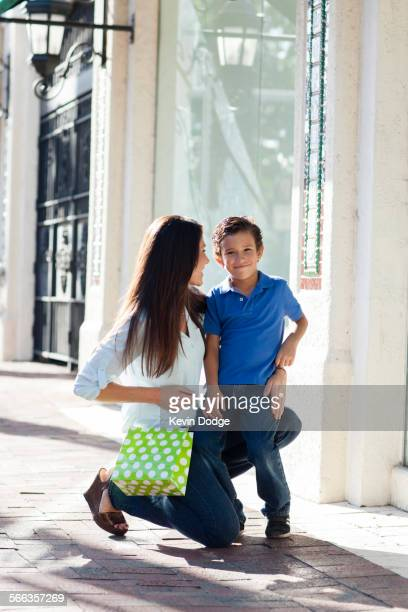Caucasian mother and son hugging on sidewalk