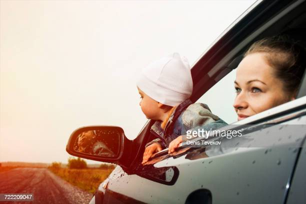 Caucasian mother and son looking out car window