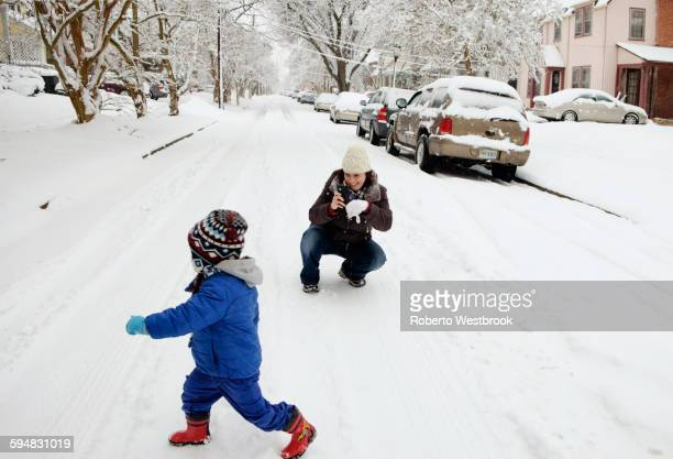 Caucasian mother and son playing in snow