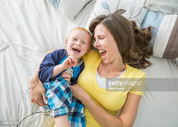 Caucasian mother and son playing on bed